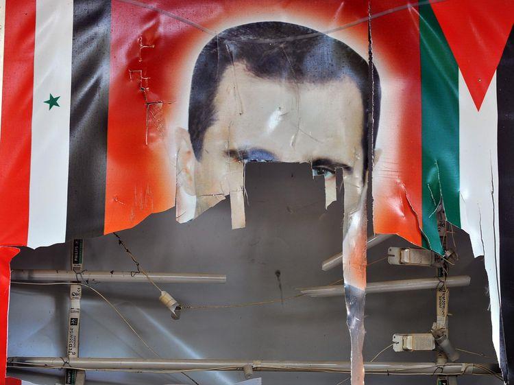 Poster déchiré du président syrien Bachar al-Assad. (Photo : BULENT KILIC.AFP)