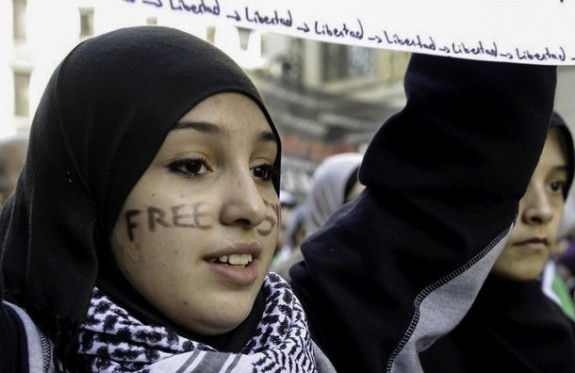 A young women demonstrates against violence in Syria. Women have led protests, delivered humanitarian relief, documented human rights violations, and negotiated with local and national decision makers, among other activities.