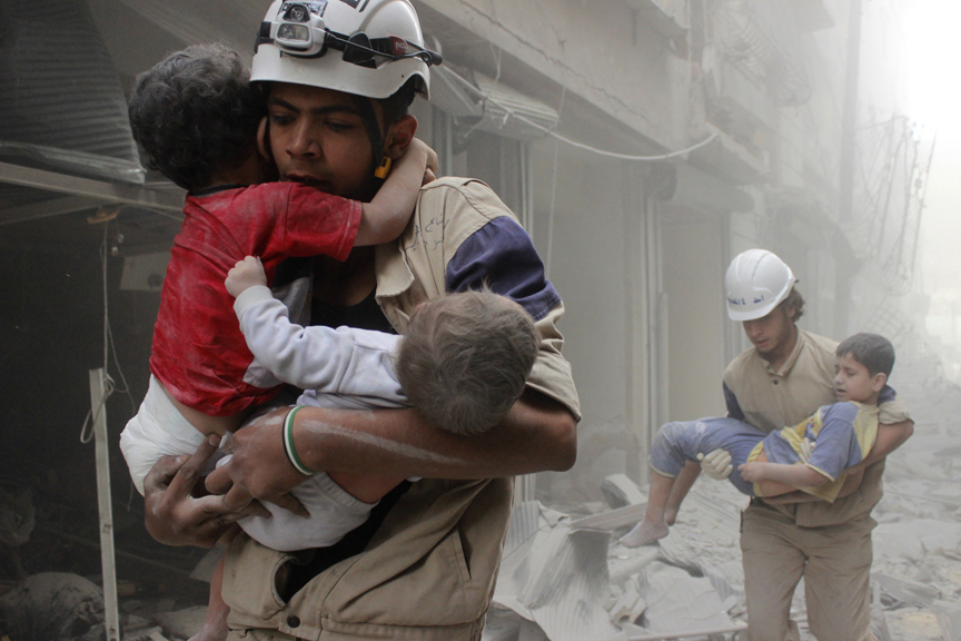 Members of the Civil Defence rescue children after what activists said was an air strike by forces loyal to Syria's President Bashar al-Assad in al-Shaar neighbourhood of Aleppo June 2, 2014. (Sultan Kitaz/Reuters)