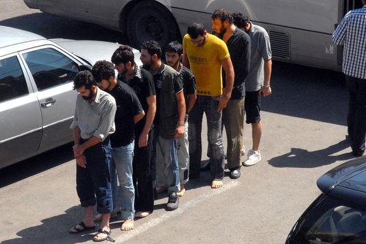 Des prisonniers arrivent au quartier général de la police à Damas en Syrie, en septembre 2012.