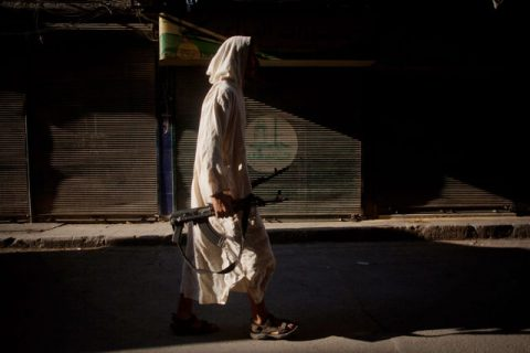 An FSA fighter walks through a street in the Bustan al-Qsar district in Aleppo, Syria, Wednesday, Sept. 12, 2012. (AP Photo/ Manu Brabo)