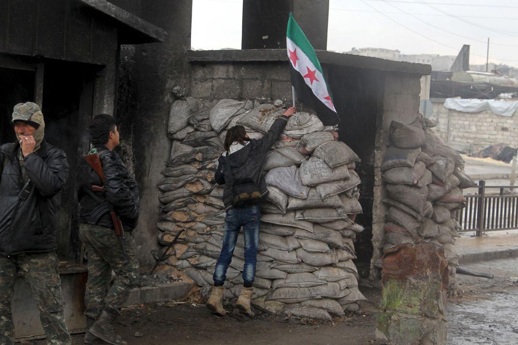 Une manifestante pour la libération des prisonniers des prisons gouvernementales syriennes dépose le drapeau de l'opposition sur un check-point contrôlé par l'Armée syrienne libre à Alep, le 24 janvier 2016.