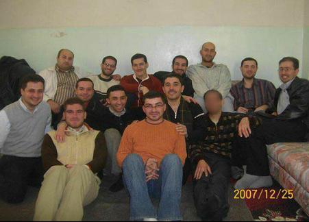 Depuis le fond à droite : Ahmad Koraytem (exil), Soleiman Shehadeh (exil), Bachar Maadamani (exil), Ammar Dokko (exil), Moataz Mourad (Daraya), Mohammed Shehadeh (Daraya), Tarek Shurbaji (exil), Mohammad Ali Kholani (détenu), Mohammad Koraytem (martyr), Mahmoud Habib (détenu), Yahia Shurbaji (détenu), Oussama Nasser (présent à Douma), Nabil Shurbaji (détenu)