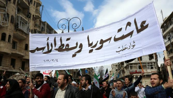 "Syrian civilians and activists hold a banner reading in Arabic ""Long live Syria, down with Assad"" during an anti-regime demonstration in the rebel-controlled side of Aleppo, on March 4, 2016"