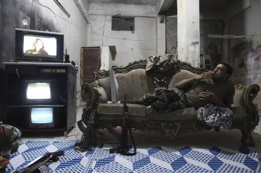 Un soldat de l'Armée syrienne libre regarde la télévision à Alep en 2013. (REUTERS/Muzaffar Salman)