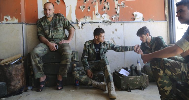In this photo taken on Wednesday, Oct. 14, 2015, Syrian Army soldiers rest during fighting in Jobar, Damascus, Syria. Backed by Russian airstrikes, the Syrian army has launched an offensive in central and northwestern regions. (Alexander Kots/Komsomolskaya Pravda via AP) RUSSIA OUT