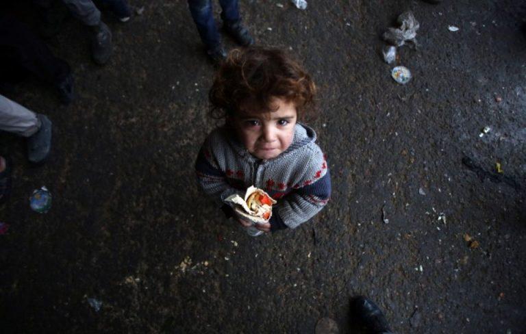 Un enfant syrien, qui a fui dans les zones d'Alep tenues pas les forces rebelle, vient de recevoir un sandwich, le 1er décembre 2016, dans un refuge dans le quartier de Jibrin, à l'est d'Alep.Photo Youssef Karwashan/AFP