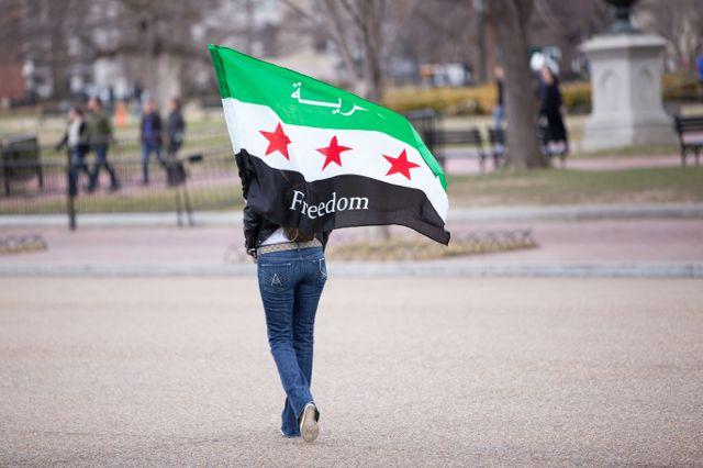Une femme porte un drapeau pour la liberté en Syrie.